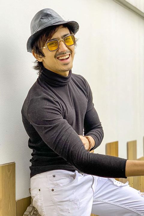 Adnaan Shaikh in black shirt and white jeans