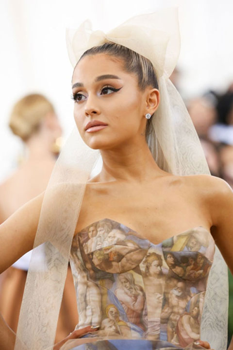Ariana Grande in sleeveless dress and white head bow