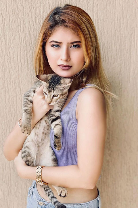 Arishfa Khan is holding her cat and wearing purple blouse and blue jeans.