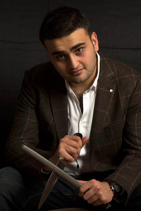 Burak Ozdemir sharpening knife while wearing brown check coat