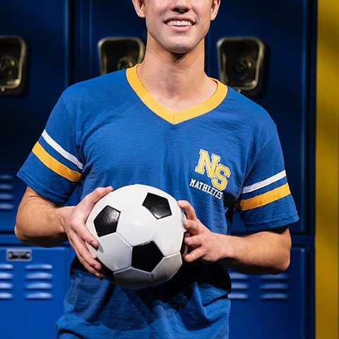 Cameron Dallas in blue shirt and football in his hands