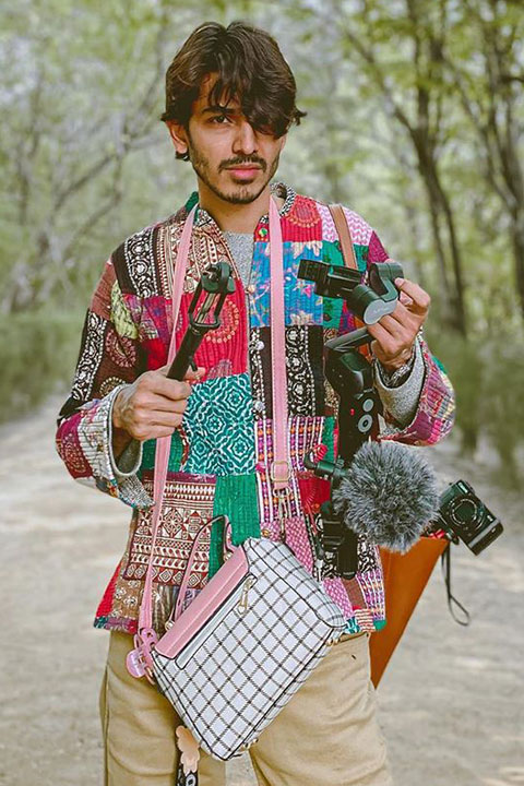 Farhan Khan holding all photography set and his girlfriend's purse. With his hair's falling perfectly on his one eye