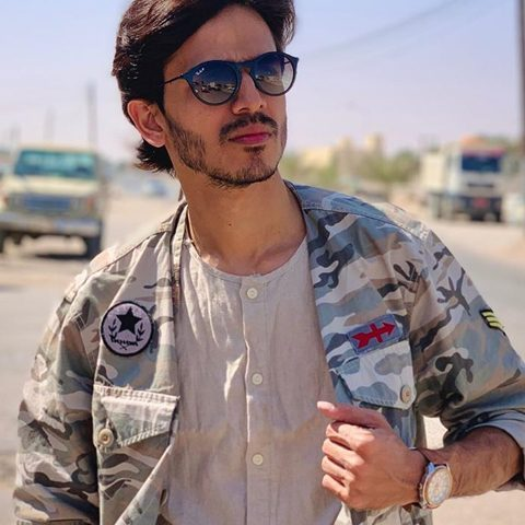 Farhan Khan wearing army style jacket and black glasses with rolex watch. He is looking handsome in his stubble