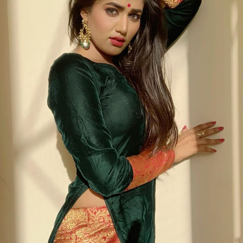 Garima Chaurasia is wearing dark green shirt and adding bold touch in traditional dress by exposing her belly.