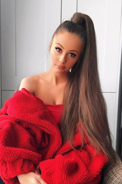 Holly H wearing red top. She has long bun and perfect tan.