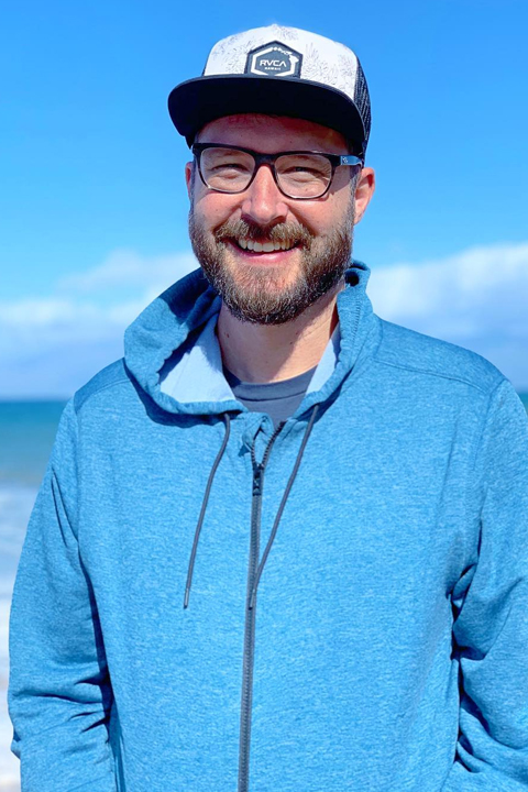 Jason Coffee in blue hoodie. Smiling at camera with sea in his background