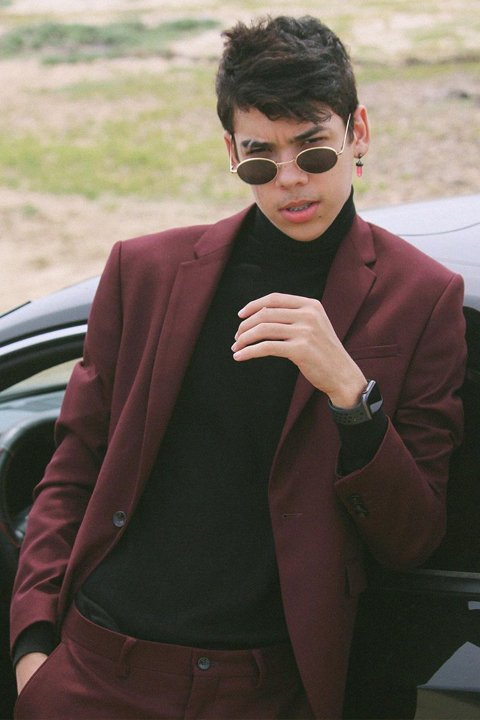 Jayden Croes wearing red suit, black high neck and Apple watch. He is leaning on super car