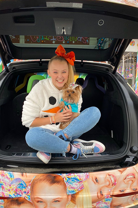 Jojo Siwa with cute dog in her hands and orange bow on her head