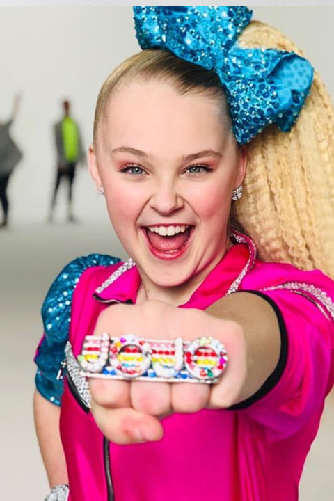 Jojo Siwa happy in pink dress and wearing blue head bow