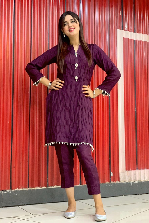 Kanwal Aftab weaing all purple dress and posing with both of her hands on her waist