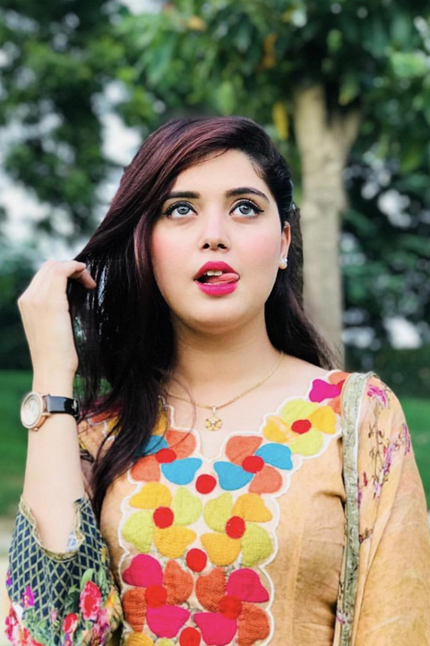 Kanwal Aftab wearing watch and licking upper lip
