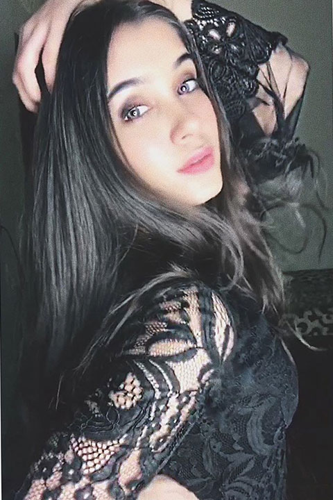 Reeja jeelani posing with her hand on her back and wearing black dress