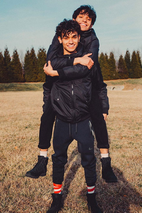 The Dobre Twin wearing all black and looking cute while hoping over each other.