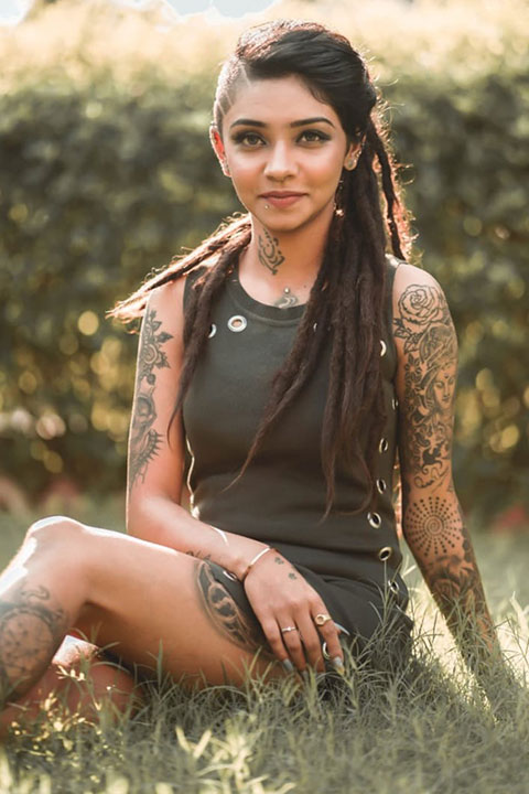 Wish Rathod in green dress sitting on grass, showing her tattoos and beautiful smile