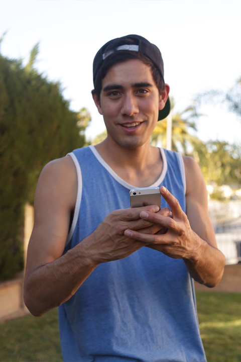 Zach King in blue vest holding I phone 6