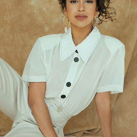 liza koshy is looking hot in white dress and posing for a picture beautifully.