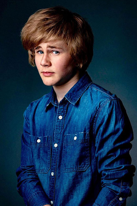 Casey Simpson with long hairs and blue shirt