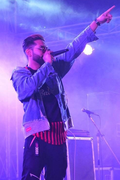 Honey King HK is pointing towards his fans during concert