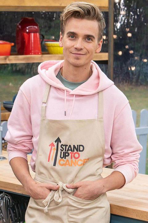 Joe Sugg as chef in pink upper and apron. Smiling for viewers