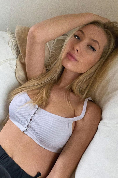 Kaylen Ward lying in her bed wearing white top and passing her hand through her hair