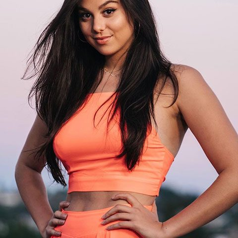 Kira Kosarin is looking at the camera with a smiling face and open hair.