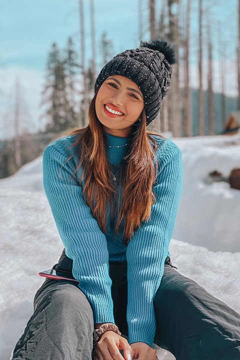 Aashna Hegde wearing blue jersey , black pent and black cap. Enjoying her vacations in snow
