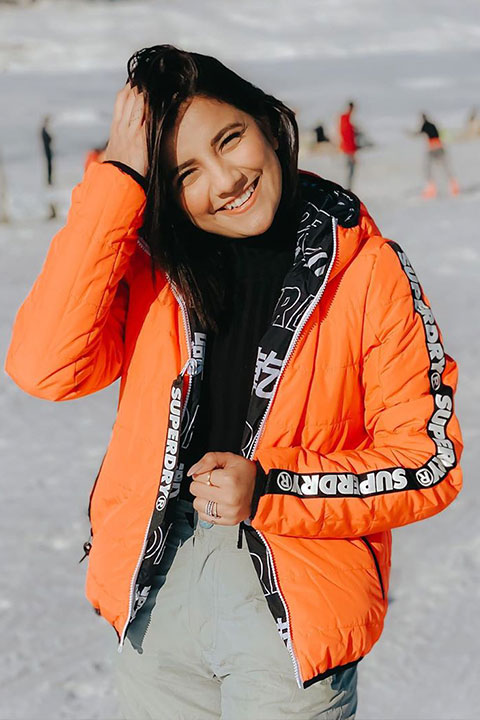 Mrunal Panchal in black shirt and orange jacket. Looking amazing with her smile on snow