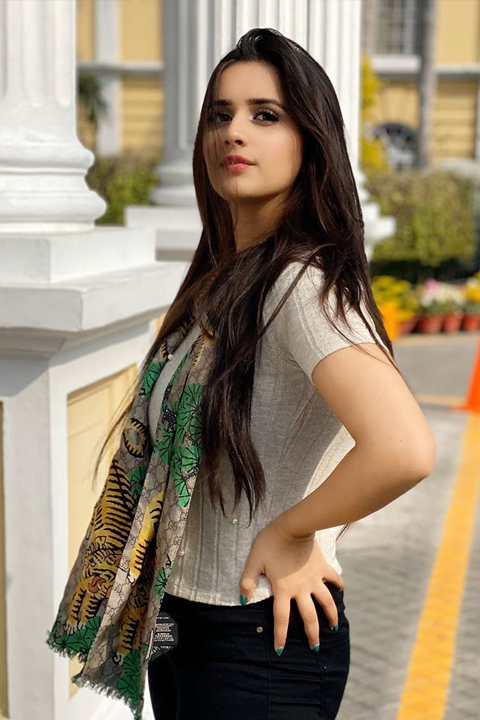 Alishba Anjum wearing white tshirt and black jeans with her hand on her hips