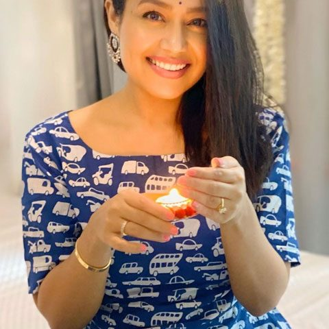Neha Kakkar in blue dress with candle in hand. looking at camera with stunning smile