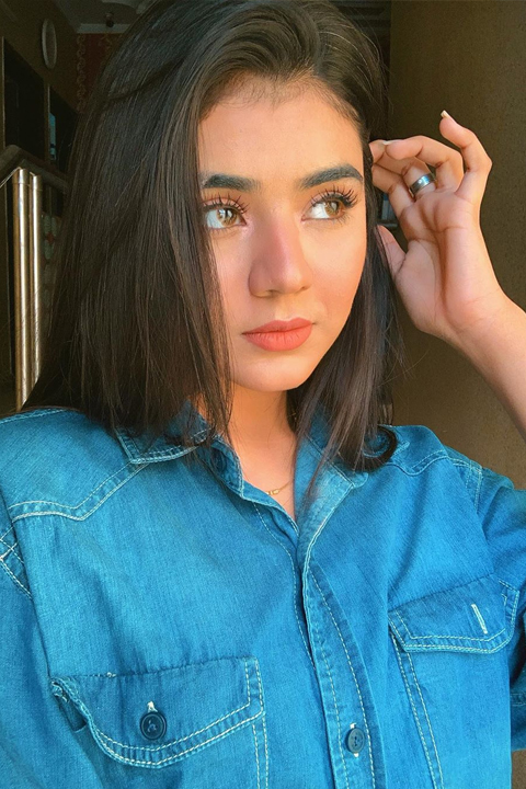 Areeka Haq in denim shirt, playing with her hair.