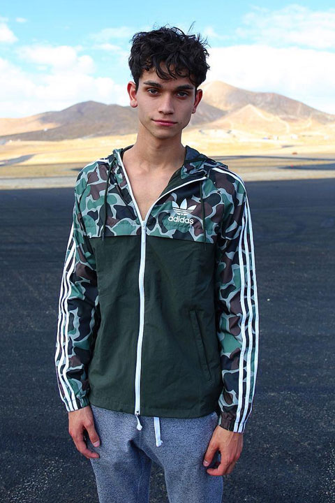 Marcus Dobre posing shirtless, wearing green hoodie and grey trousers with mountains in background.