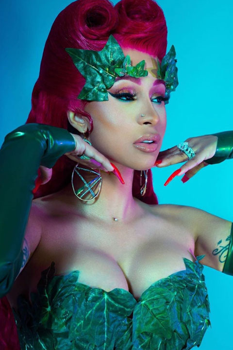 Cardi B cosplaying poison Ivy perfectly. She looks amazing in red hair and red nails. Her body is covered by leaves only.