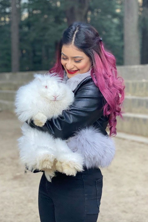 Anam Darbar holding her white pussy cat while looking at it and smiling happily. She is wearing tight black jeans and has pink stripe hair