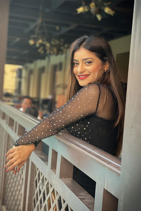 Anam Darbar wearing see through black top and smiling at camera with her perfect red lips and teeth.