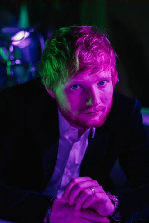 Ed Sheeran being hot and casual at party. He is looking intensely at camera with his green eyes