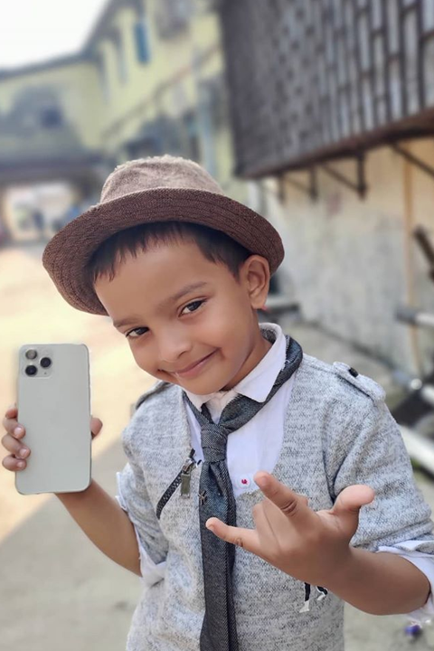 Sadim Khan holding iphone 11 and smiling at camera while making signs with his hand