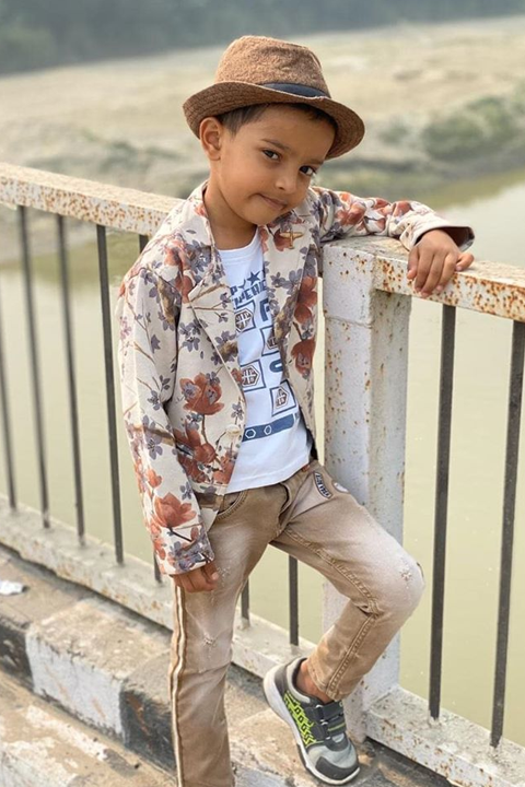 Sadim Khan being stylish and dashing with his flower coat and brown hat. He is posing on bridge