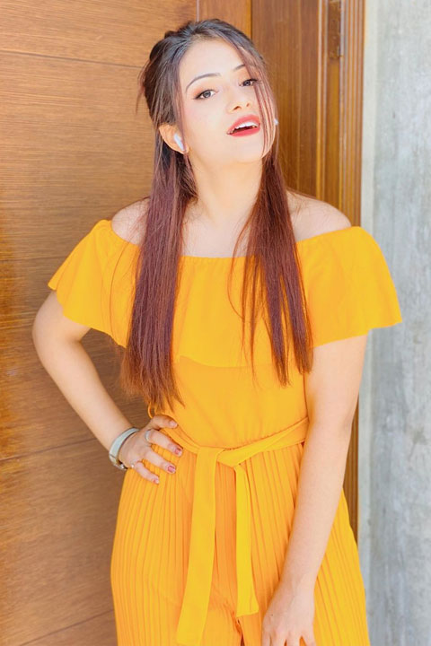 Sehar Hayyat is wearing a beautiful orange yellow dress and is posing for the camera