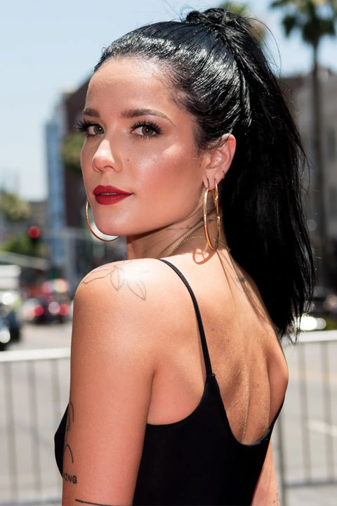 Halsey is looking beautiful in black sleeveless dress and open hair and she is wearing golden earrings.
