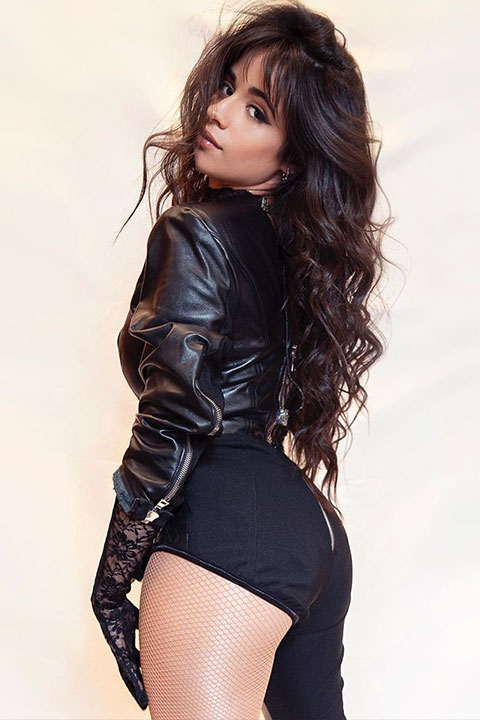 Camila Cabello is wearing black jacket and posing for a picture.
