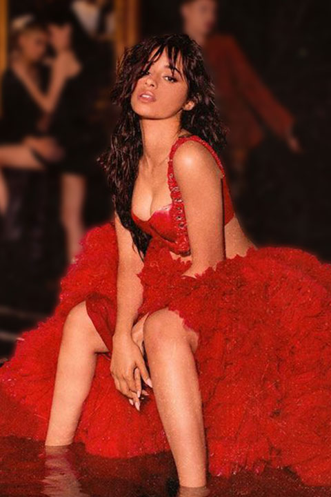 Camila Cabello is wearing red dress and her feet is in water.