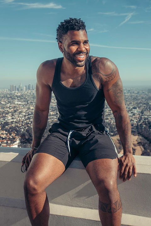 Jason Derulo seating on a wall wearing black vest and black shorts