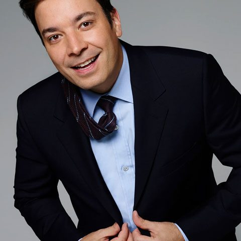 Jimmy Fallon is smiling and wearing beautiful black pent coat