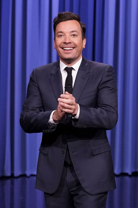 Jimmy Fallon is giving a beautiful smile and wearing dark blue pent coat