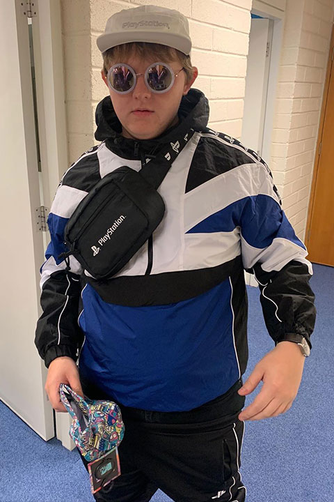 Lewis Capaldi is wearing a skin colour cap and tie a bag on chest