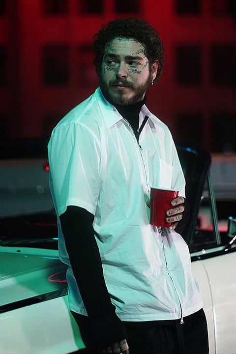 Post Malone holding red cup in white shirt and black pent
