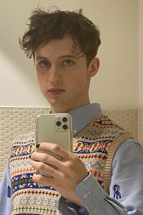 Troye Sivan taking selfie in blue shirt and sweater
