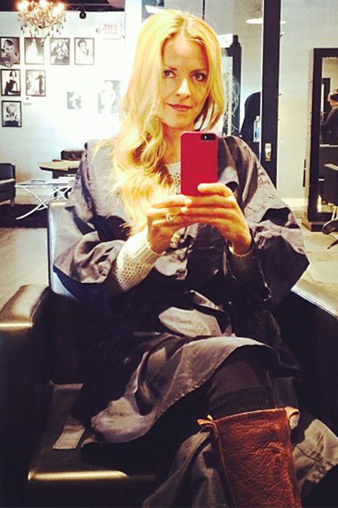 Kim Challan is sitting in a salon and taking selfie