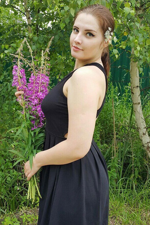 Klubni4ka Liza is standing at the park and holding flowers in her hand and she is wearing black sleeveless dress.