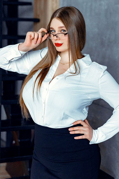 Luccy Sofia is holding her glasses and she is wearing white shirt and dark blue jeans.